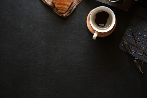 Home office desk space with coffee, croissant and copy space Premium Photo