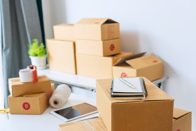 Home office of startup online business seller, showing table with cardboard boxes, tablet, smartphone, notebook and equipments. online selling, entrepreneur, work at/from home concept. Premium Photo