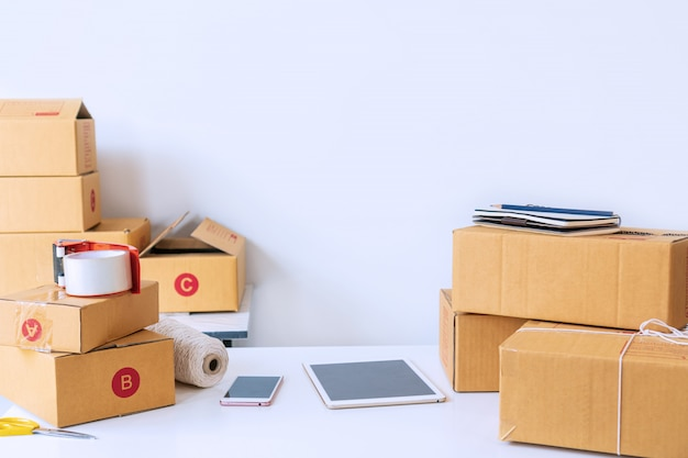 Home office of startup online business seller, showing table with cardboard boxes, tablet Premium Photo
