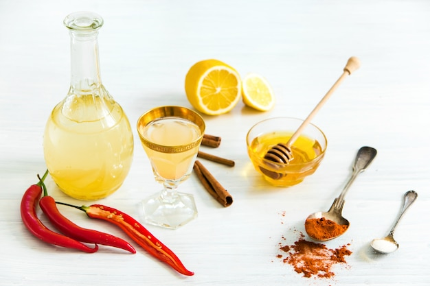 Home red pepper tincture in a glass and fresh lemons on wooden table Free Photo