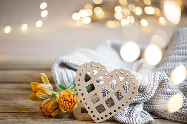 Домашний романтический натюрморт с деревянным декоративным сердцем и связанным элементом на размытом фоне с боке. Бесплатные Фотографии