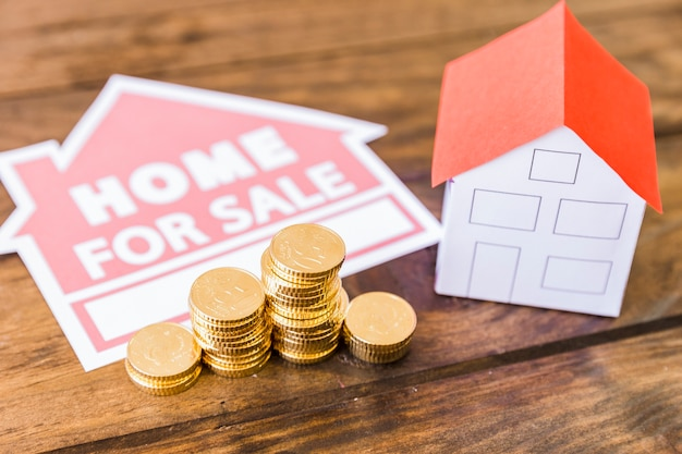 Home for sale icon with stacked coins and house on desk Free Photo