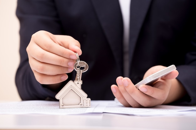 Home seller holding home key. concept for real estate business. Premium Photo