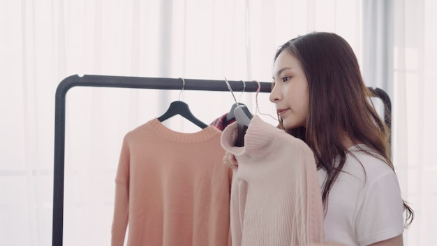 Home wardrobe or clothing shop changing room. asian young woman choosing her fashion outfit clothes Free Photo