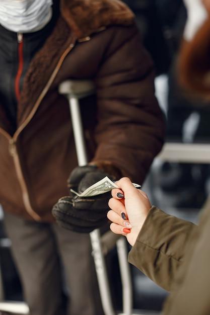 冬の街でホームレス。食べ物を求める男。 無料写真