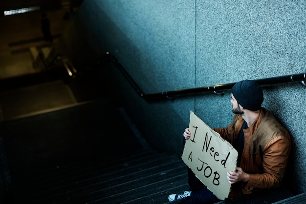 Homeless man asking for job sitting on stairway sidewalk Free Photo
