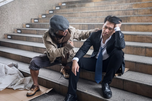 Homeless man cheer up sad businessman Premium Photo