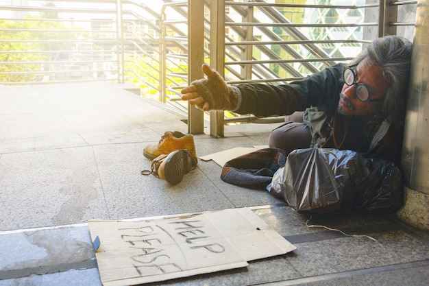 """A homeless man is sitting on walkway in town. he is show label """"help please """"word. Premium Photo"""