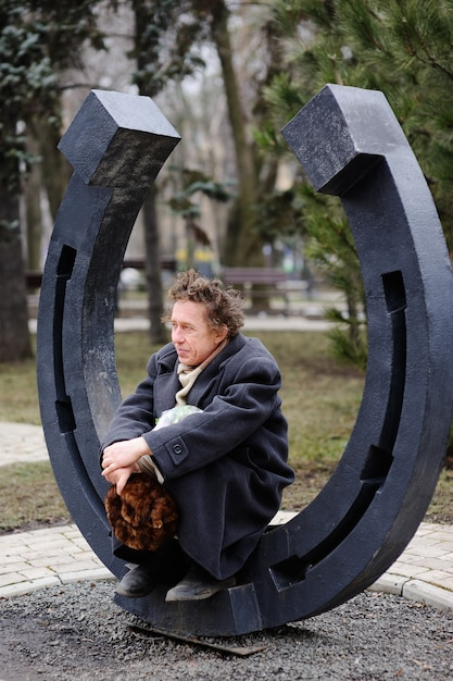A homeless man sitting in a large horseshoe Premium Photo