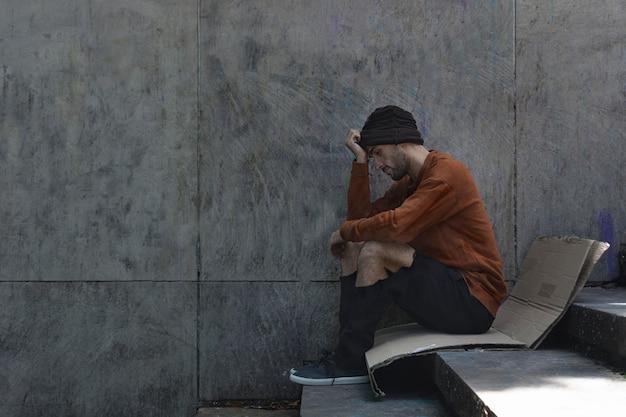 Homeless man sitting sideways on cardboard Free Photo