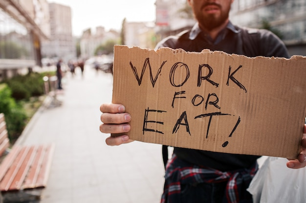 Homeless man standing outside and holding a cardboard which says work for eat Premium Photo