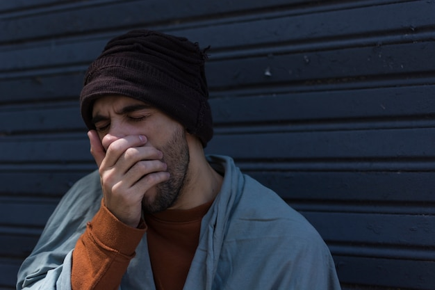 Бездомный мужчина зевает и прикрывает рот Бесплатные Фотографии