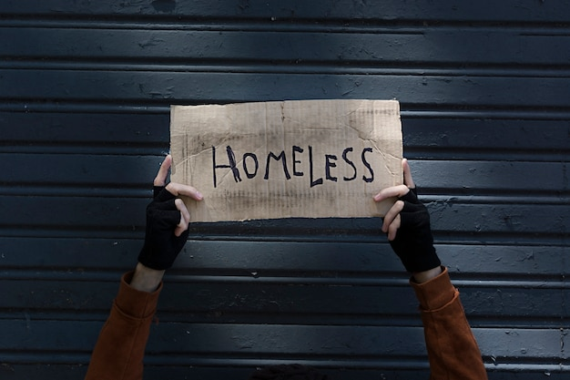 Homeless sign held by a beggar hands Free Photo