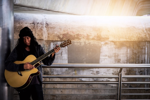Homeless, stand up, guitar, sing for donations. Premium Photo