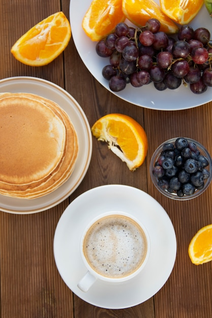 Homemade american pancakes with cup of coffee and fruits. wooden table. Premium Photo