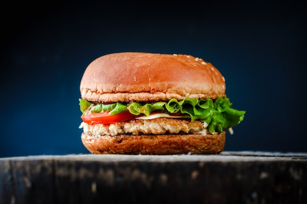 Homemade appetizing chickenburger on black background. Premium Photo