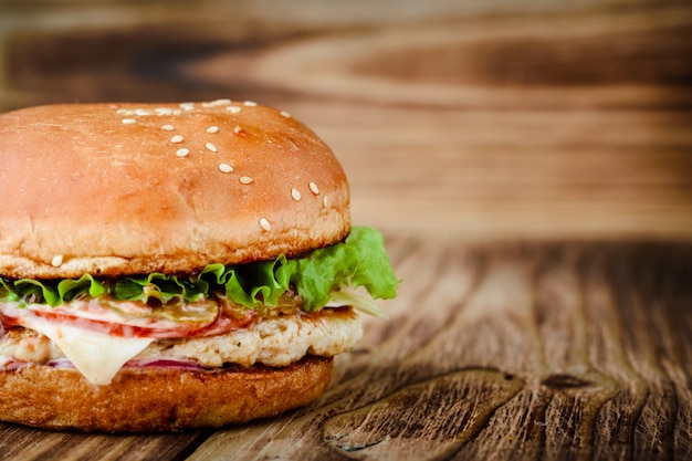 Homemade appetizing chickenburger on a wooden background Premium Photo