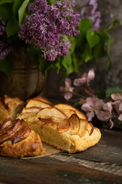 Homemade apple cinnamon scones with lilac flowers and apple blooming branches Premium Photo