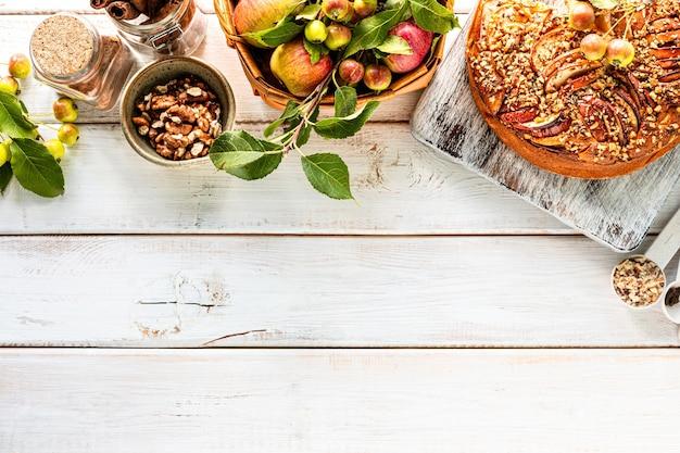 白い木製の背景に自家製アップルパイと食材。上面図。コピースペース 無料写真