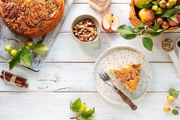 白い木製の背景に自家製アップルパイと食材。上面図。 無料写真