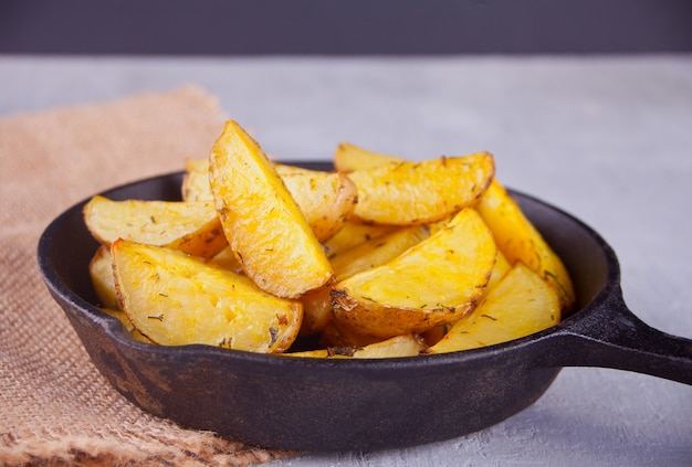Homemade baked potato wedges with herbs on black iron pan on the gray background. Premium Photo