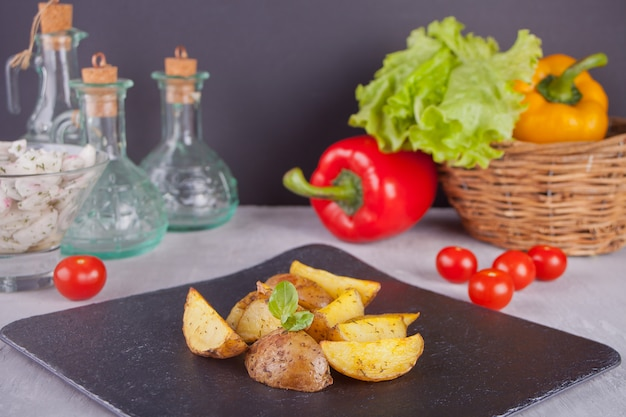 Homemade baked potato wedges with herbs on a black plate with vegetables on the background Premium Photo