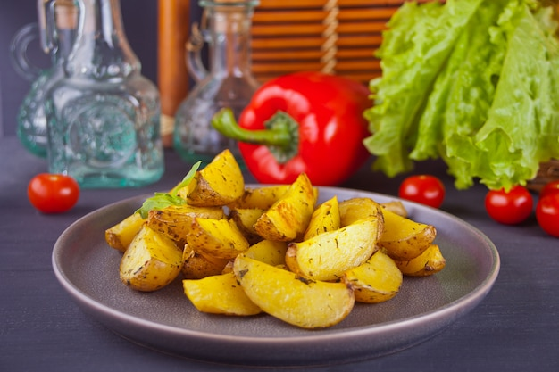 Homemade baked potato wedges with herbs on gray plate with vegetables on the background. Premium Photo