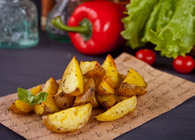 Homemade baked potato wedges with herbs with vegetables on the background. Premium Photo