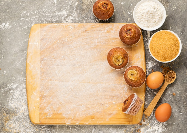 Homemade banana muffins and cooking ingredients are laid out on a cutting wooden board. Premium Photo