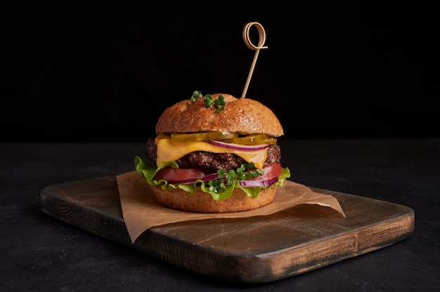 Homemade beef burger with cheese, tomatoes, red onions, cucumber and lettuce on black slate over dark background, unhealthy food, copy space Premium Photo