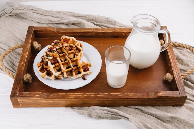 Homemade belgian waffles with fresh milk on wooden tray Free Photo