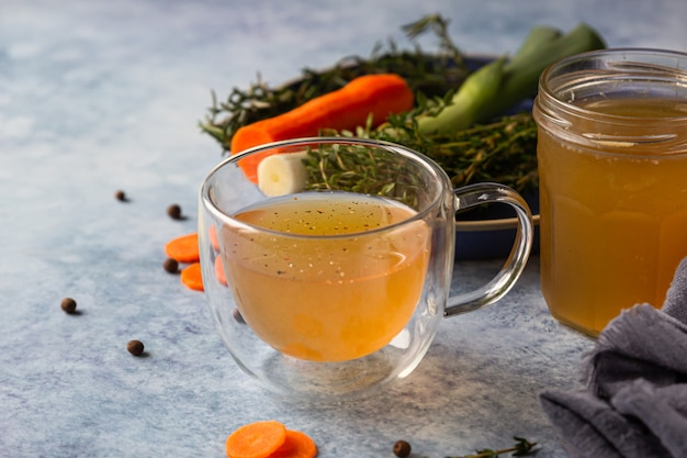 Homemade bone broth in glass mug and vegetables. collagen source for the body. Premium Photo