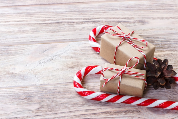 Homemade box with a red bow near christmas candy canes Premium Photo