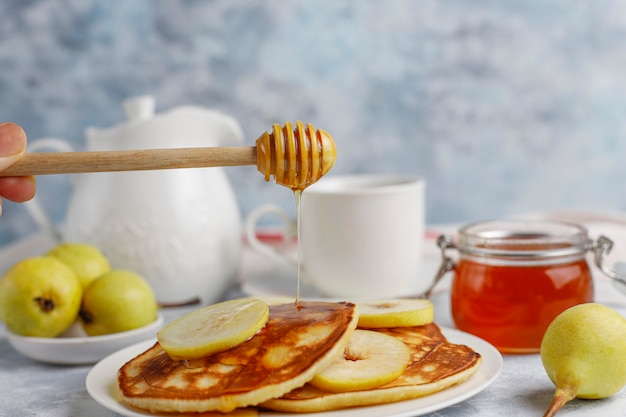 Homemade breakfast: american style pancakes served with pears and honey with a cup of tea on concrete . top view and copy Free Photo