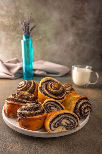 Homemade buns with poppy seeds on a white plate bowl of lavender and cap with milk on a dark background closeup selective focus Premium Photo