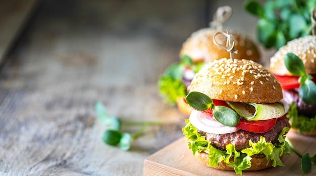Домашние котлеты с котлетой, свежий салат, помидоры, лук на деревянном столе. копировать пространство Бесплатные Фотографии