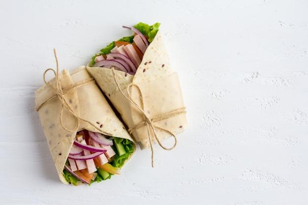Homemade burritos with vegetables, ham and tortilla Premium Photo