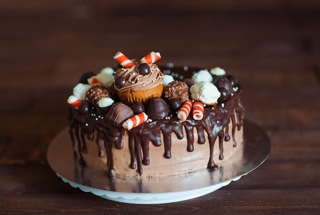 Homemade cake decorated with sweets, cupcakes and waffles. Premium Photo