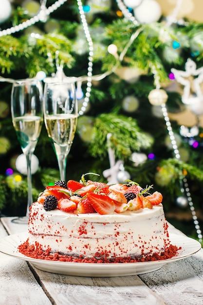 Домашний торт red velvet, украшенный сливками и ягодами на новогоднем фоне Premium Фотографии