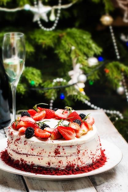 Домашний торт красный бархат, украшенный кремом и ягодами над елкой Premium Фотографии