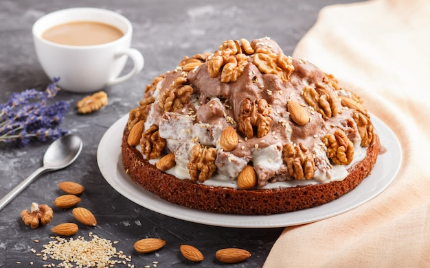 Homemade cake with milk cream, cocoa, almond, hazelnut with orange textile and a cup of coffee. side view. Premium Photo
