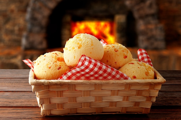 Homemade cheese bread, traditional brazilian snack, in the basket after leaving the oven on a rustic kitchen table Premium Photo