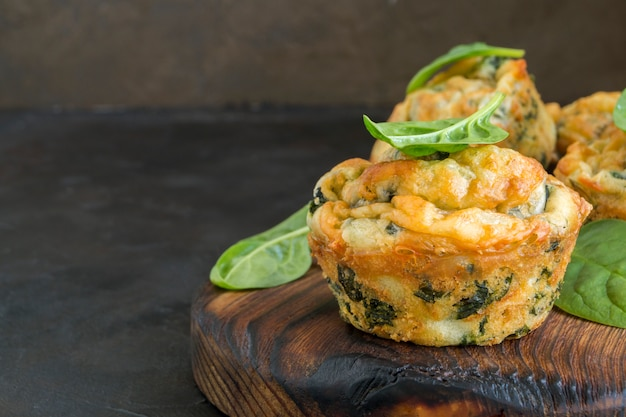 Homemade cheese muffins with spinach. on dark background. Premium Photo