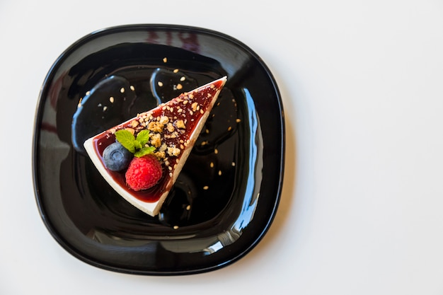 Homemade cheesecake with fresh raspberry; blueberry and mint for dessert on black plate over white background Free Photo