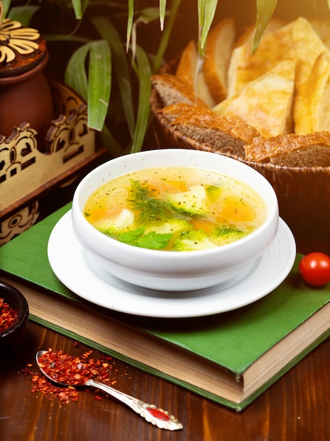 Homemade chicken vegetable soup, overhead view on a book on the table Free Photo