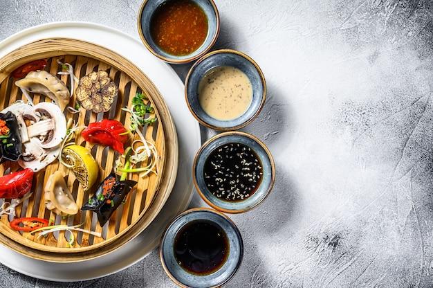伝統的な竹蒸し器で自家製中国と韓国の餃子を提供しています。灰色の背景。上面図。コピースペース Premium写真