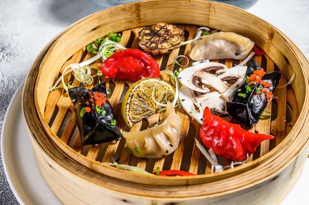 伝統的な竹蒸し器で自家製中国と韓国の餃子を提供しています。灰色の背景。上面図 Premium写真