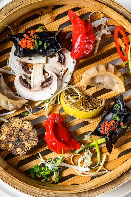 自家製の中華料理と韓国の餃子を伝統的な竹蒸し器で提供しています。灰色の背景。上面図 Premium写真