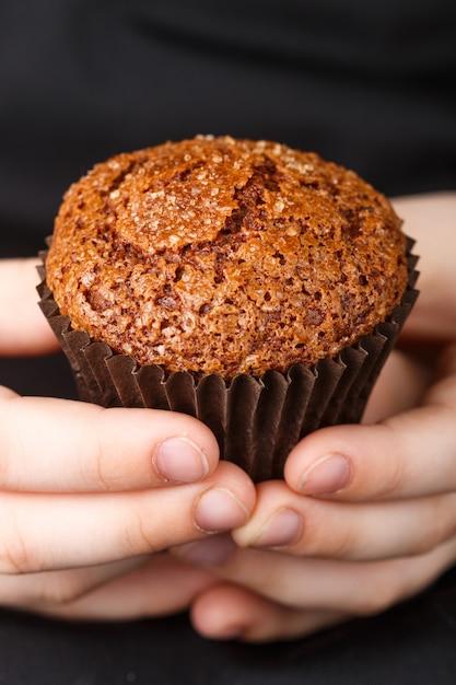 Homemade chocolate muffin with caramel (sugar) crust in the children's hands Premium Photo