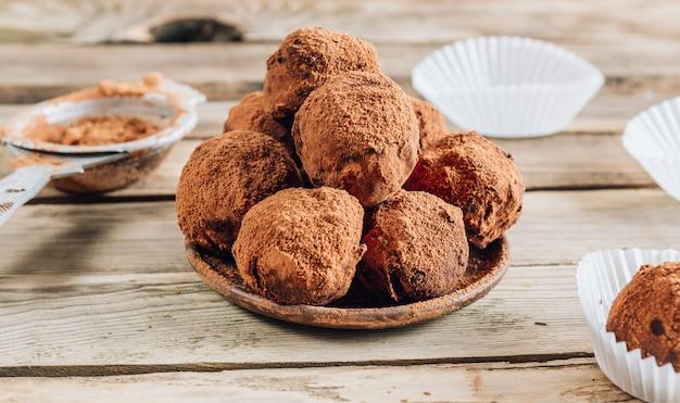 Rustcの木製の背景にココアを振りかけた皿の上の自家製チョコレートトリュフキャンディボール。トップビュー Premium写真